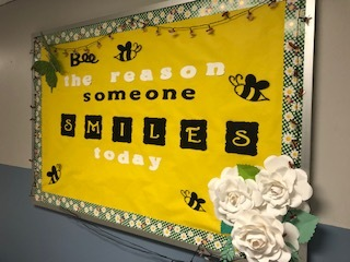 "Yellow bulletin board, statement ""Bee The Reason Someone Smiles Today"""